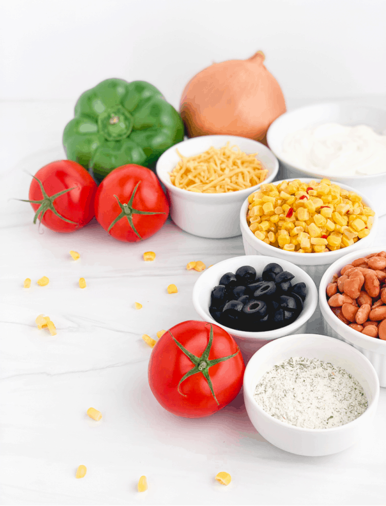 Mexicorn Dip Ingredients with Peppers, Tomatoes, Mexicorn, Pinto Beans, Sour Cream, Ranch Seasoning, Cheese, and Olives