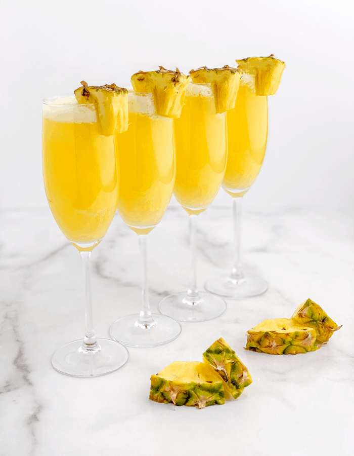 Pineapple mimosas in a line with pineapple garnishes
