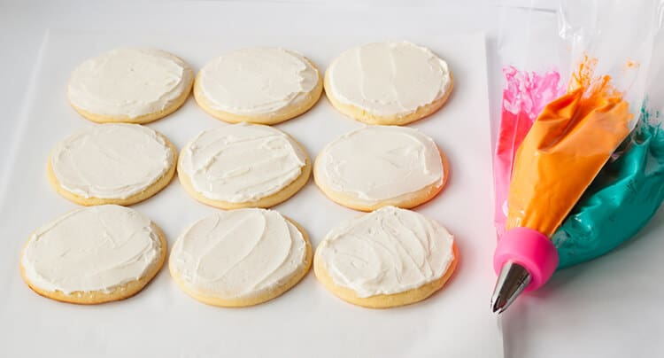Frosted white sugar cookies with tri color piping bag