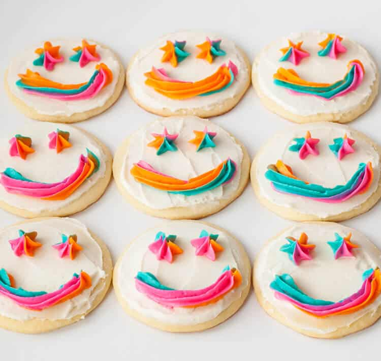 Frosted sugar cookies with piped smiley faces